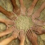 Hands in a circle in the sand